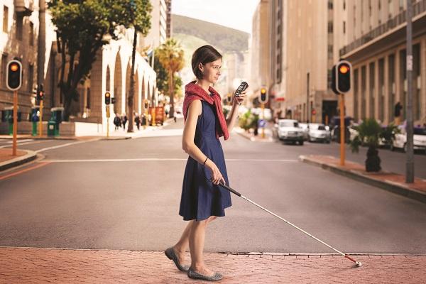 Bild på kvinna som korsar en gata med Victor Trek i handen
